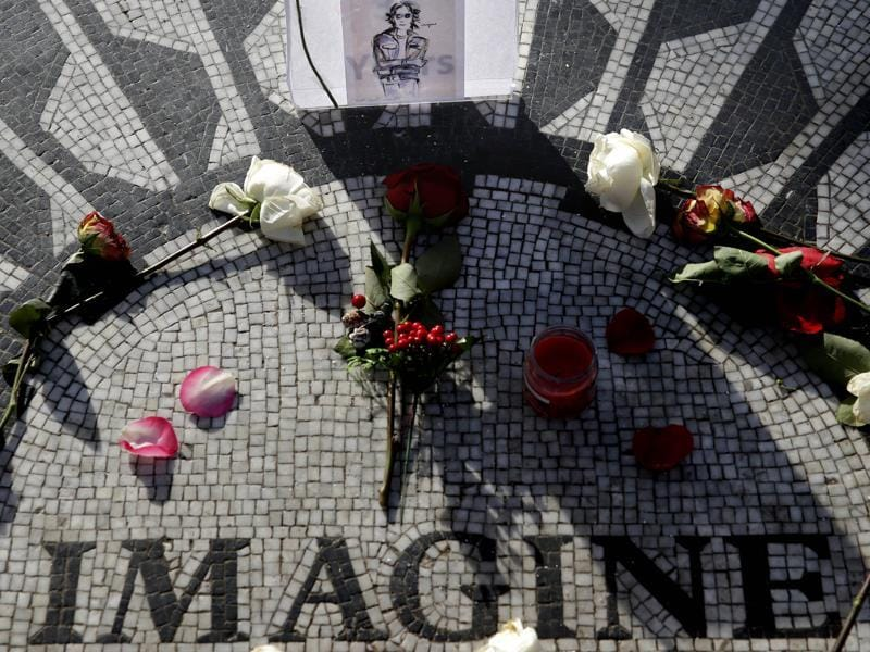 A picture of John Lennon is surrounded by flowers at Strawberry Fields, the site that pays tribute to Lennon, in Central Park, New York, on December 7. Tuesday is the anniversary of Lennon's death. (AP)