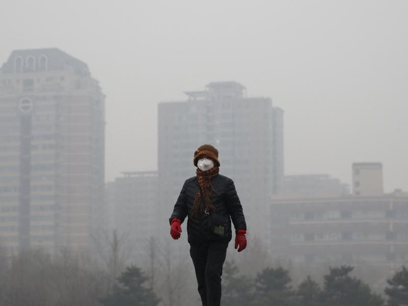 A woman wearing a protective mask takes a walk at a park in the morning on an extremely polluted day in Beijing. (REUTERS)