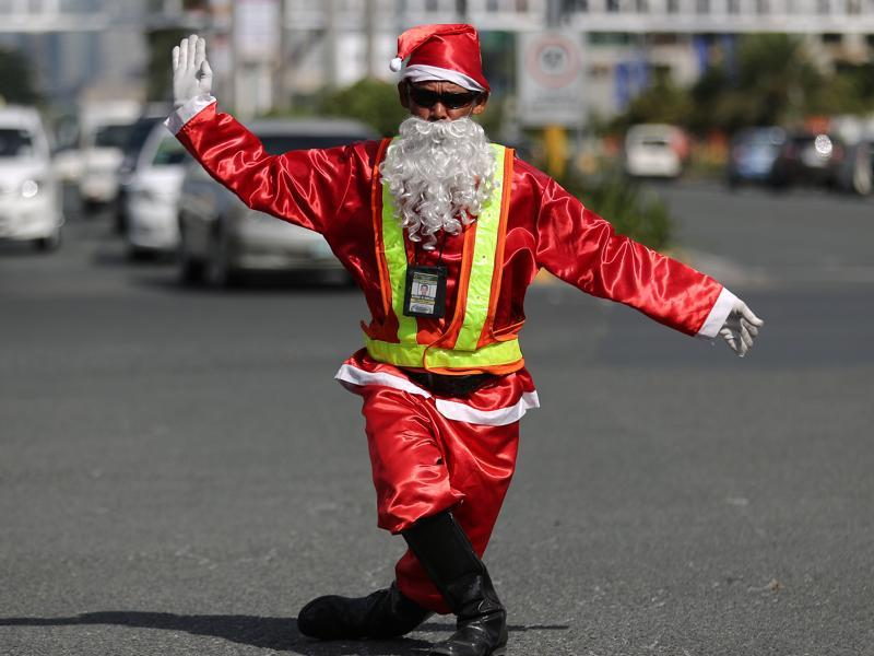 Filipino traffic enforcer Ramiro Hinojas dressed in a Santa Claus costume directs a flow of vehicles in a dancing way along a busy intersection in suburban Pasay, south of Manila, Philippines, Tuesday, December 8, 2015. Hinojas said his dance moves were influenced by Michael Jackson and hopes that people will be entertained as they wait during the Christmas gridlock. (AP)