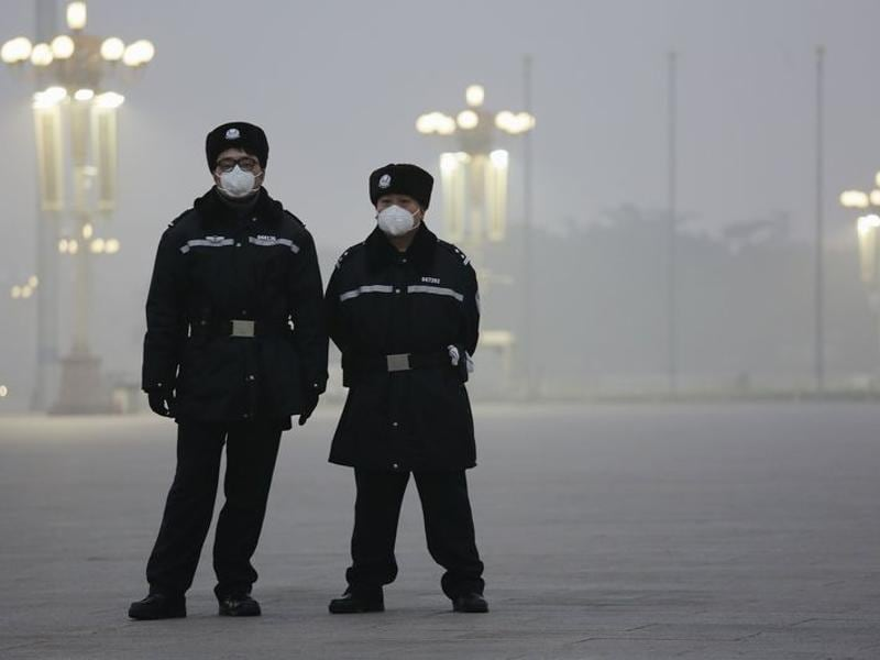 Policemen wear protective masks at the Tiananmen Square on an extremely polluted day as hazardous, choking smog continues to blanket Beijing. (REUTERS)