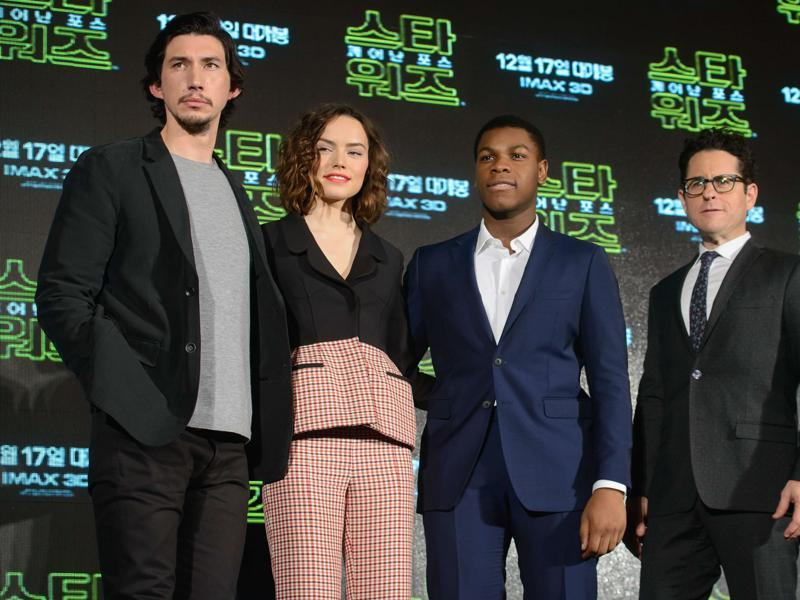 Star Wars: The Force Awakens' cast members Adam Driver, Daisy Ridley, John Boyega, and director JJ Abrams pose for photos following a press conference to promote the film in Seoul. (AFP)