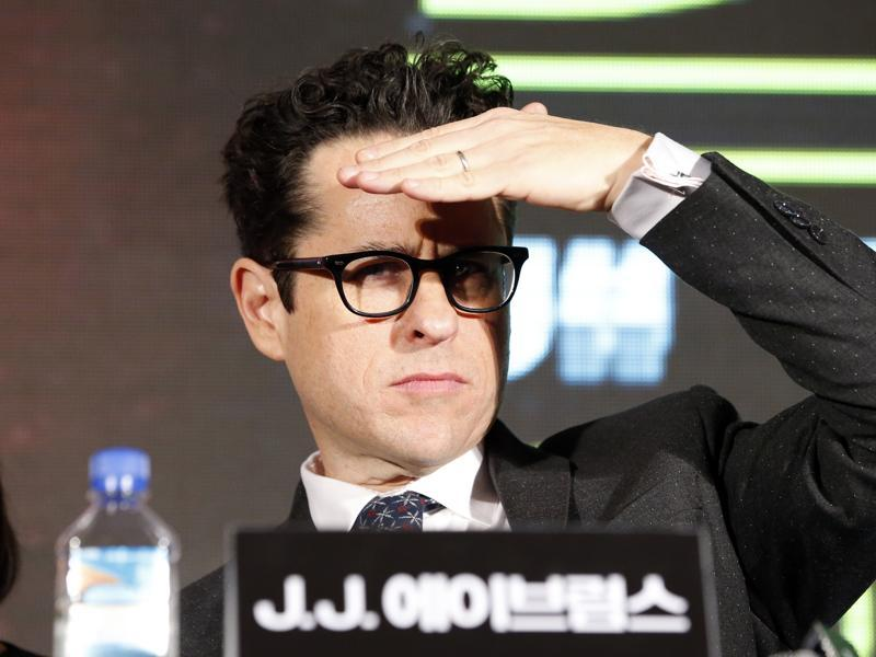 Director JJ Abrams covers his eyes, blocking the stage lighting as he surveys the crowd during a press conference for his new movie Star Wars: The Force Awakens, in Seoul, South Korea. (AP)