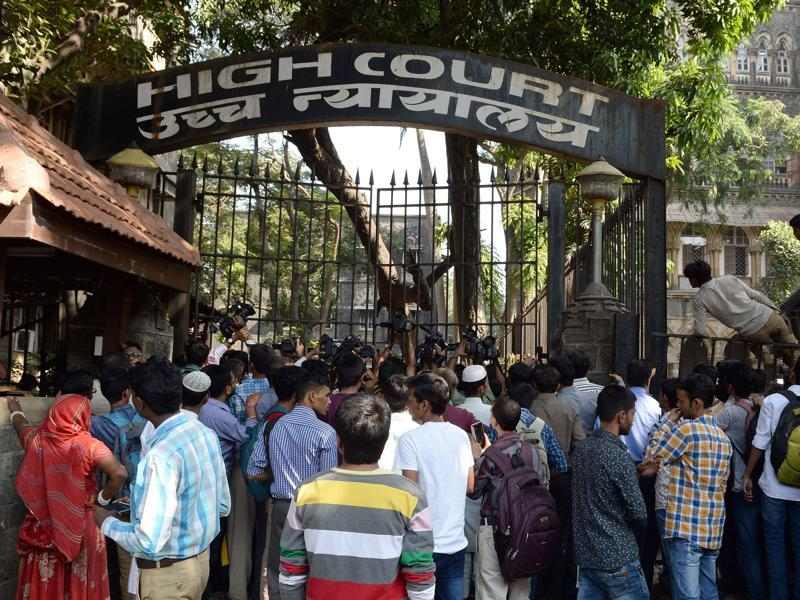 Bystanders cling onto the iron fencing of Bombay high court in Mumbai on Thursday , as they attempt to catch a glimpse of Salman Khan after being acquitted of culpable homicide in the 2002 hit-and-run case. (AFP)