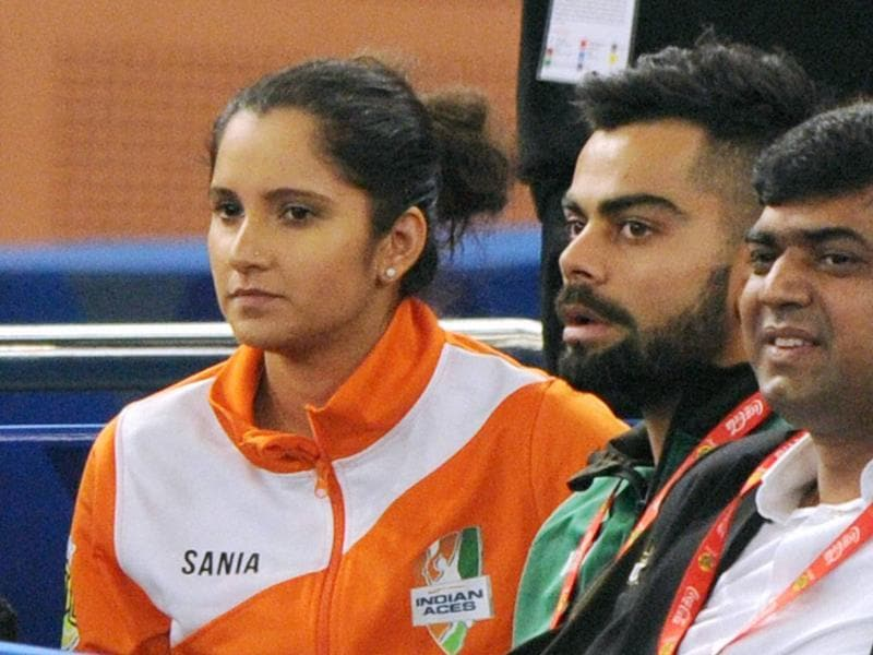 Indian cricket team captain Virat Kohli with Tennis player Sania Mirza watching the men's doubles match at International Premier Tennis League (IPTL) at IG stadium in New Delhi on Thursday. (PTI)
