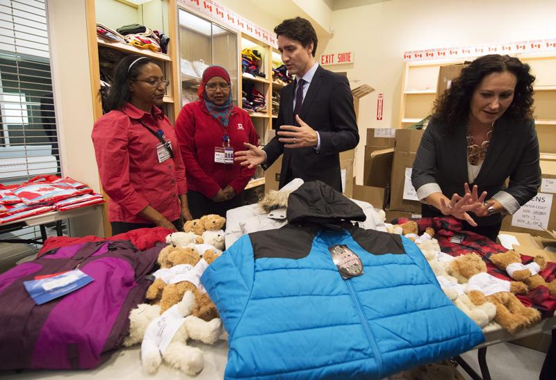 Canadian Prime Minister Justin Trudeau looks over winter clothing which was to be handed out to arriving Syrian refugees before their arrival at the Pearson International airport, in Toronto. (AP Photo)