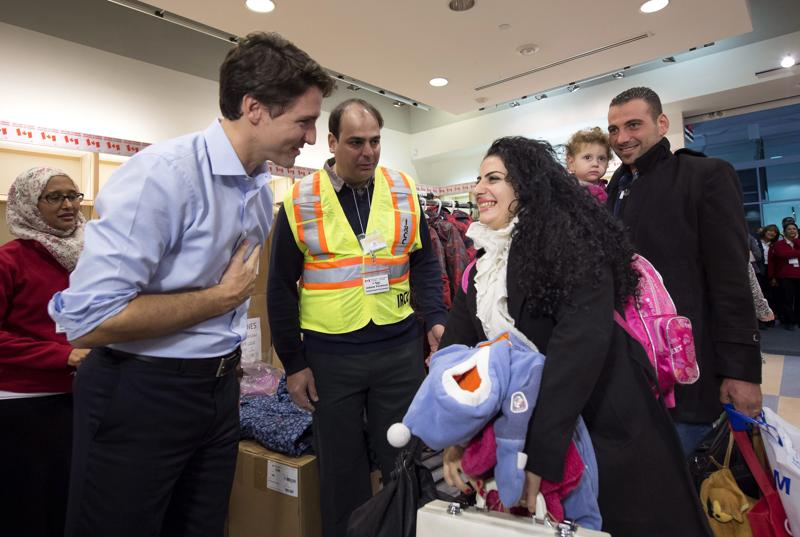 Canadian PM Justin Trudeau (L) greets Georgina Zires, Madeleine Jamkossian  and her father Kevork Jamkossian -- refugees fleeing from Syria -- as they arrive at the Pearson International airport, in Toronto. (The Canadian Press via AP )