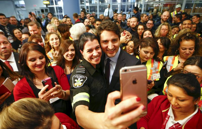 Canada's Prime Minister Justin Trudeau poses with airport staff as they await Syrian refugees arriving at the Toronto Pearson International Airport in Mississauga, Ontario. (Reuters )