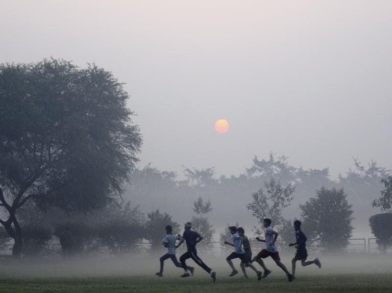 People exercising in a park in the capital in the fog. (Sunil Ghosh / HT Photo)