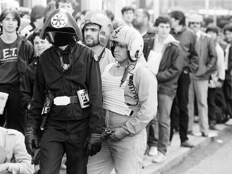 In this May 25, 1983 file photo, three costumed fans of the Star Wars movie trilogy, Kevin Maguire, from left, as an Imperial Fire Control Officer, Stephen Robards, and his brother John Robards as Rebel Fighter Pilots, stand in a line of ticket buyers outside a Boston theatre, before the first showing there of the film Return of the Jedi. The effect Star Wars has had on movies is as colossal as the Death Star itself and to some, just as fearsome. (AP)