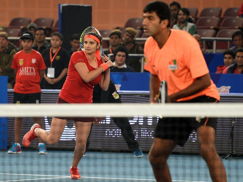 India's Sania Mirza of the Indian Aces plays a shot past partner and compatriot Rohan Bopanna during the International Premier Tennis League (IPTL) tennis match between Indian Aces and Philippine Mavericks in New Delhi. (AFP)