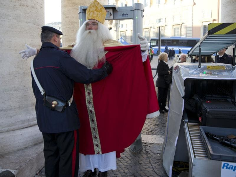 Germany's Wolfgang Kimmig-Liebe, who has been volunteering as Santa Claus for years, is searched by a Carabiniere paramilitary police officer before entering in St. Peter's Square at the Vatican to attend Pope Francis general audience, Wednesday, December 2, 2015.  (AP)