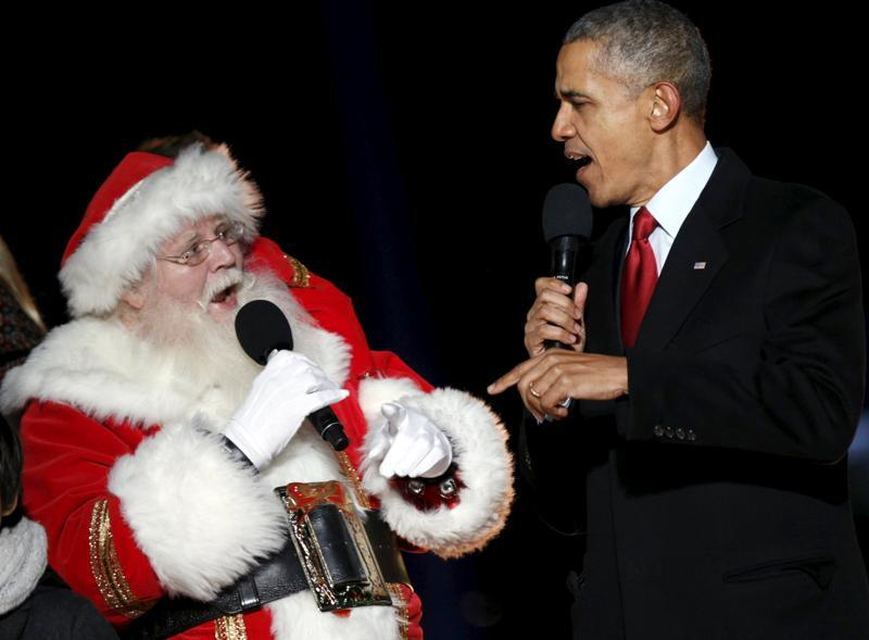 US President Barack Obama and a man dressed as Santa Claus sing onstage during the National Christmas Tree Lighting and Pageant of Peace ceremony on the Ellipse in Washington December 3, 2015.  (REUTERS)