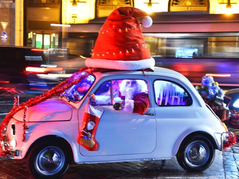 A man dressed as Santa Claus drives an old Fiat 500 car at Piazza Venezia square in central Rome on December 13, 2015. (AFP)