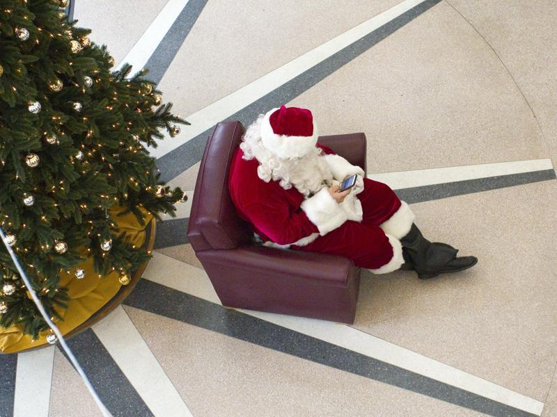 Santa Clause checks his cellphone while waiting for University of Idaho students who want to be photographed with him at the Idaho Commons in Moscow, Idaho, on Wednesday, Dec. 2, 2015.  (AP)