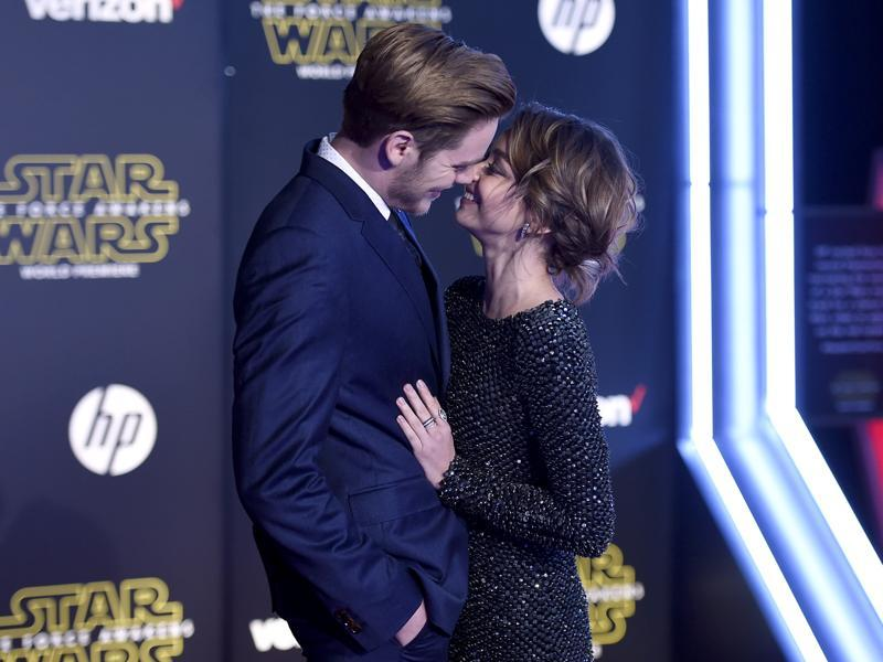 Dominic Sherwood, left, and Sarah Hyland kiss as they arrive at the world premiere of Star Wars: The Force Awakens at the TCL Chinese Theatre. (AP)