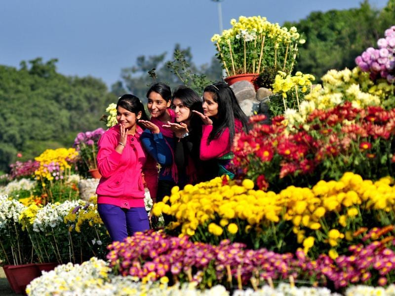 Girls pose for a picture as they soak in the festivities at the Chrysanthemum Show being held at the Panjab University in Chandigarh.  (Ravi Kumar/HT Photo)