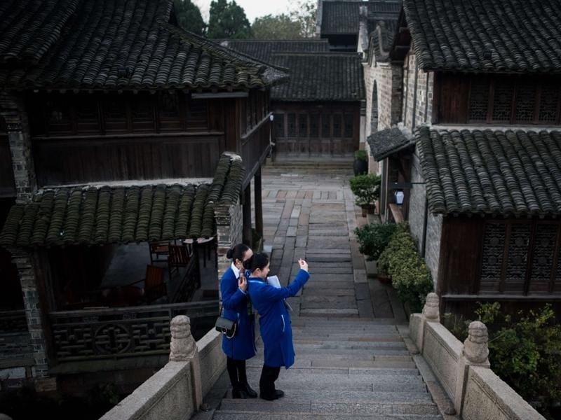 Volunteers take a selfie at dawn in Wuzhen, China where the World Internet Conference takes place, on December 16, 2015. (AFP)