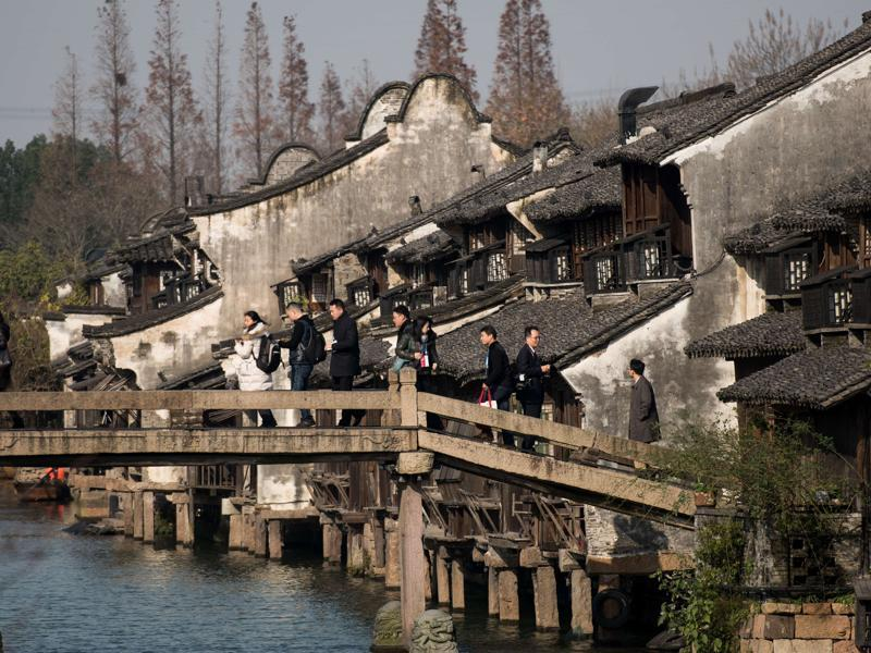 Participants cross a bridge to enter the World Internet Conference venue in Wuzhen, China, December 16, 2015. Officials from technology giants including Nokia, Apple, Kaspersky, IBM and Samsung are expected to attend.  (AFP)