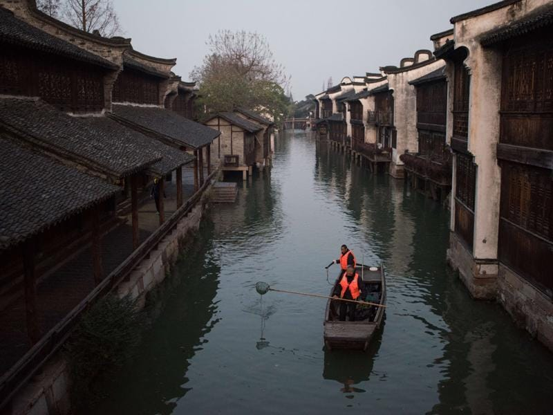 Canal cleaners go about their chores in Wuzhen in China's Zhejiang province, where the World Internet Conference takes place, at dawn on December 16, 2015. Ancient stone bridges, stone pathways and delicate wood carvings are reminiscent of Wuzhen's legacy. (AFP)