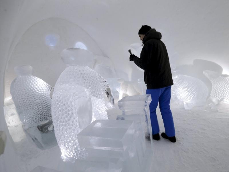 A man takes a picture of a room. Guests are given sleeping bags, survivalist advice, tips on toilet trip management on ice and a sauna in the morning to burn off the frostbite. (REUTERS)