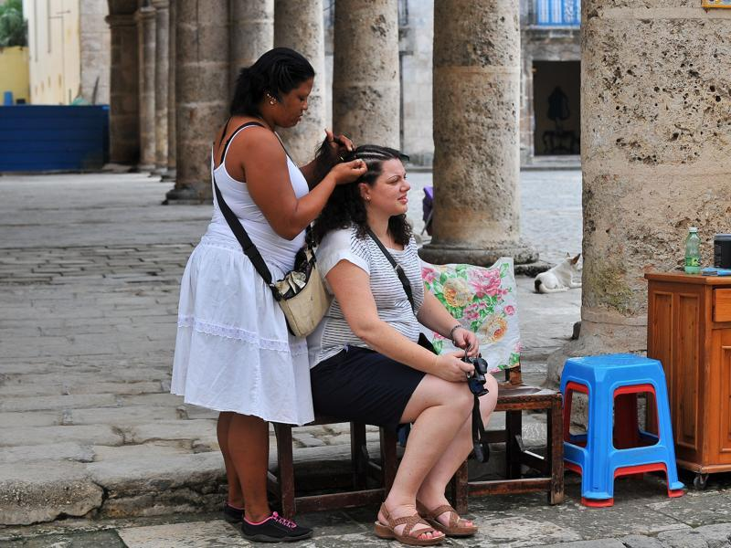 A tourist gets her hair done at the Old Havana, on December 16, 2015.Cuban culture is a unique mix of Spanish, African, French, Asian and English ways of life. (AFP)