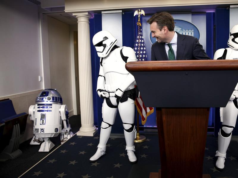 White House press secretary Josh Earnest and Star Wars Stormtroopers wait for R2-D2  to enter the briefing room after US President Barack Obama finished his end of the year news conference at the White House. (REUTERS)
