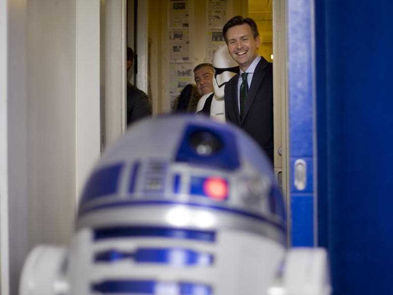 White House Press secretary Josh Earnest smiles as he watches R2D2 interact with members of the media during a surprise visit to the Brady Press Briefing Room of the White House. Star Wars movie characters will greet children of Gold Star families who are attending a special screening of Star Wars The Force Awakens at the White House Family Theater.  (AP)