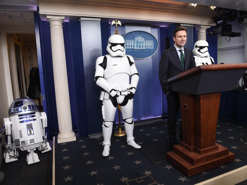 US Press Secretary Josh Earnest speaks to the press in the briefing room at the White House with Star Wars characters R2D2 and Storm Troopers. The new Star Wars movie The Force Awakens was shown at the White House for children of military families. (AFP)