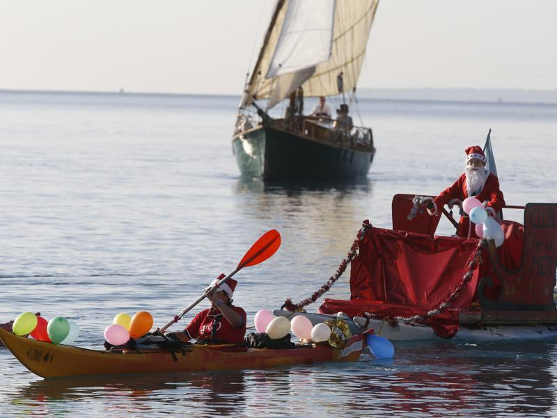 People dressed as Santa Claus attend the traditional Christmas bath in the Mediterranean Sea in the French riviera city of Nice, southeastern France. (AFP)