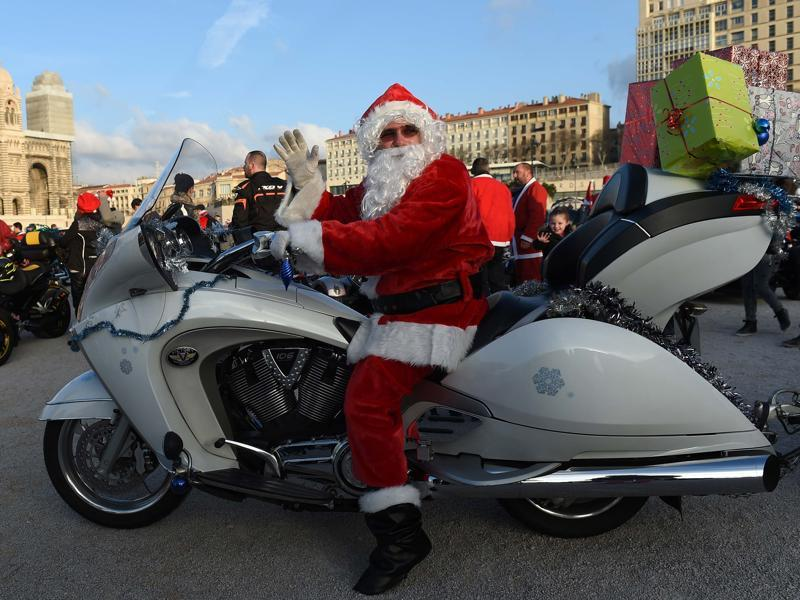 A biker dressed as Santa Claus drives in front of the MUCEM (The Museum for Europe and the Mediterranean) in Marseille, France.  (AFP)