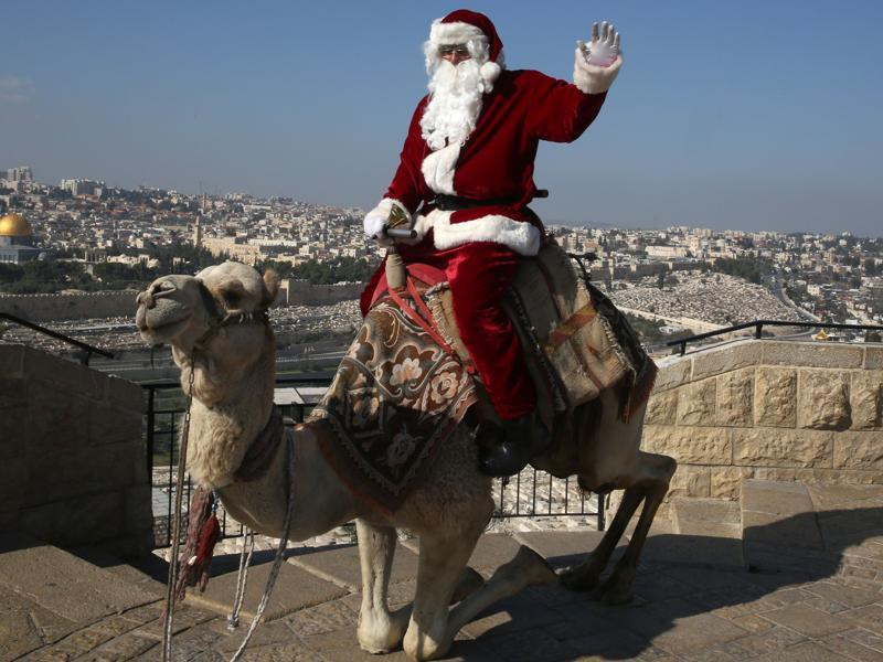 A Palestinian dressed up as Santa Claus rings a bell as he sits on a camel at Mt. Olives back-dropped by Jerusalem's Old City skyline. (AFP)