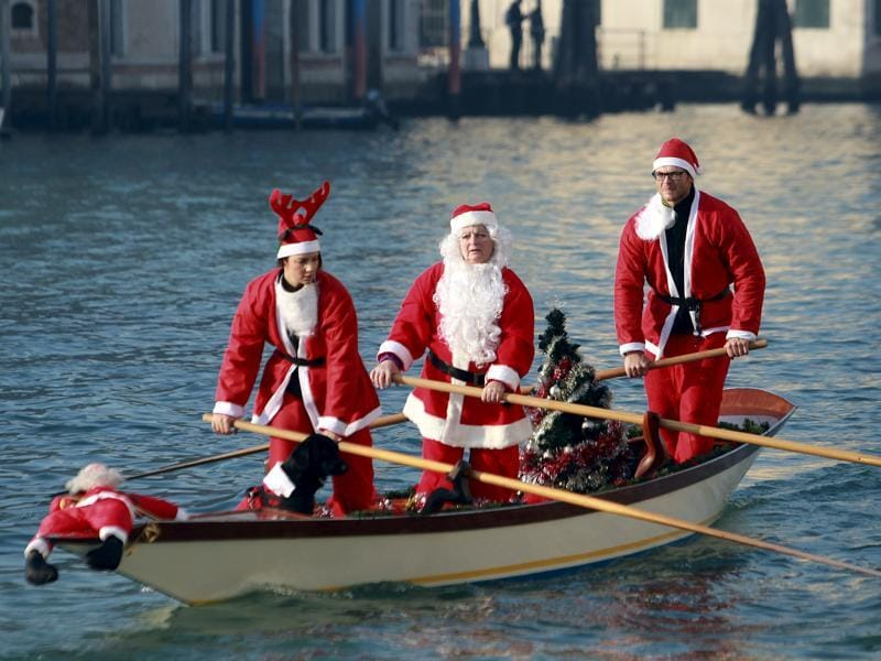 People dressed as Santa Claus row a boat on Venice's Grand Canal, in northern Italy. (REUTERS)