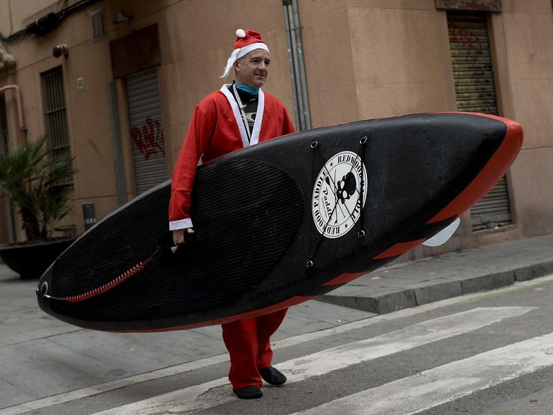 A person dressed as Santa Claus walks along a street with a paddle board to participate in a fund raiser at the beach in Barcelona. (AFP)