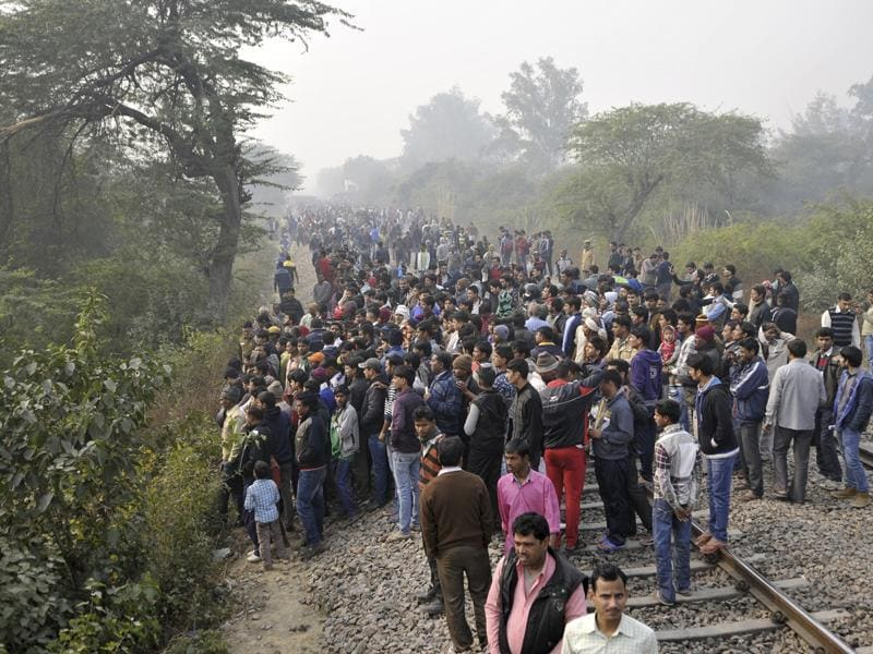 Citizens gather at the site of the crash. According to officials, Ashram Express train was passing by when the plane crashed.  (Vipin Kumar/Hindustan Times)