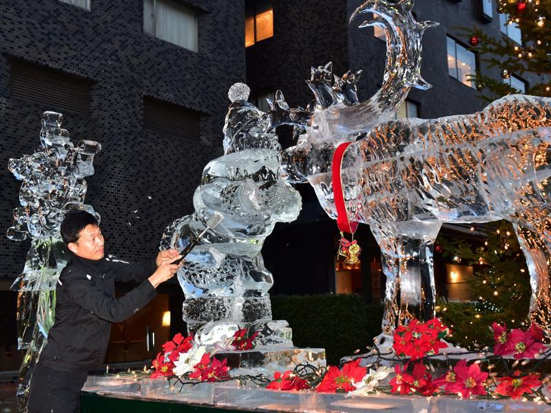 Hotel chef and world ice carving champion Yoshihito Kosaka shaves ice to make a 1.8-metre Santa Claus and reindeer at a hotel in Tokyo. (AFP)