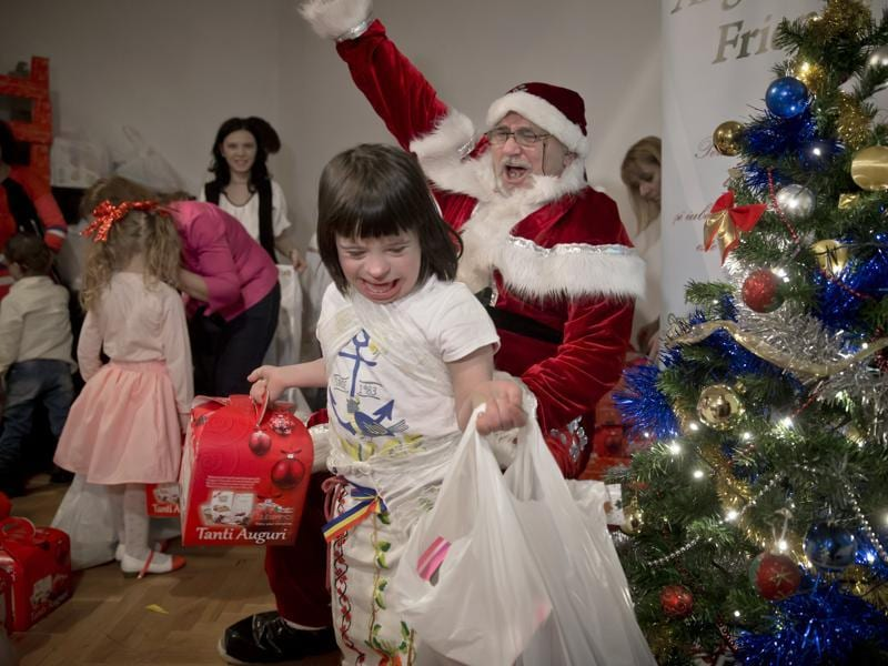 Eight years old Maia laughs walking away with presents received from a man dressed as Santa Claus during a Christmas party for children affected by the Down Syndrome, organized by the Angels Down Friends association in Bucharest, Romania.  (AP)