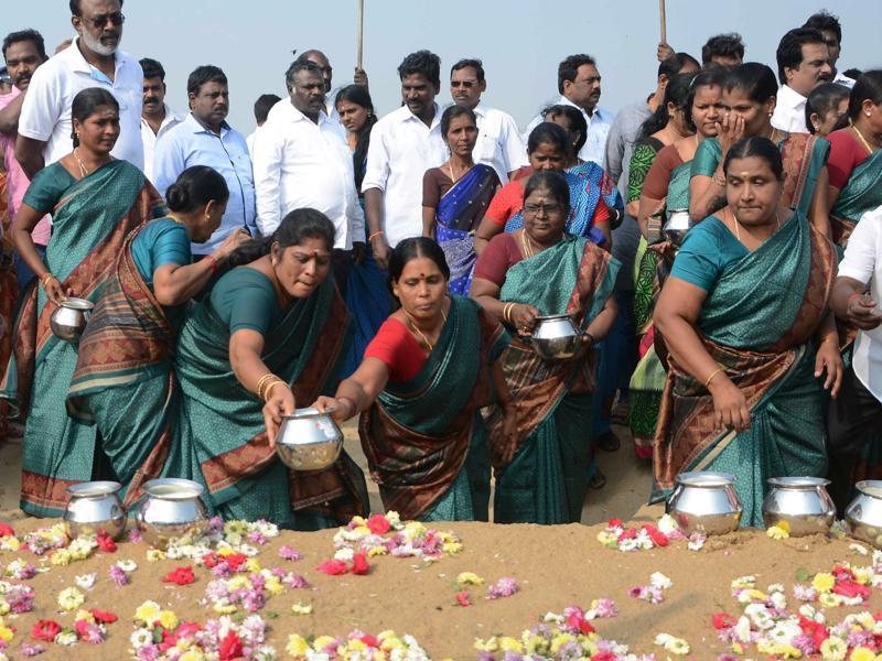 Women leave pots of milk as offerings during a ceremony for the victims of the 2004 earthquake and tsunami, at Marina Beach in Chennai. (AFP)