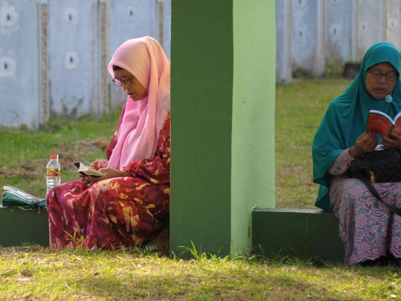 Two women pray at the Ulhee Lheue mass cemetery in Indonesia where thousands of the 2004 tsunami victims are buried. (AFP)
