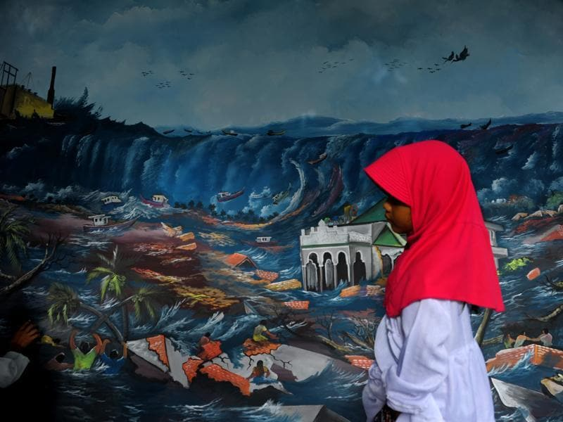 A young girl walks past a tsunami mural at a mass cemetery in Indonesia where thousands of the 2004 tsunami victims are buried. On December 26, 2004 a 9.3-magnitude earthquake off Indonesia's western tip generated a series of massive waves that pummelled the coastline of 14 countries. (AFP)