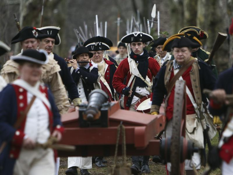 A group of Revolutionary War re-enactors haul a cannon during the re-enactment of Washington crossing the Delaware River. (AP)