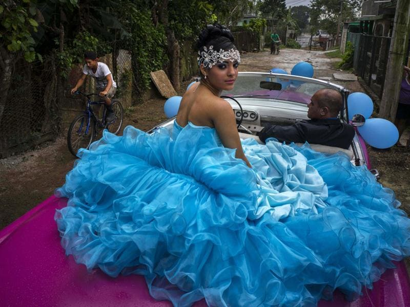 In parts of Latin America, Quinceañera is a ceremony celebrating a girl's fifteenth birthday. This birthday is celebrated differently from any other as it marks the transition from childhood to young womanhood. Daniela Santos Torres, 15, waits in a classic American car with her father Ivan Santos to ride to her quinceanera party in the town of Punta Brava near Havana, Cuba on Dec 20, 2015. (AP)