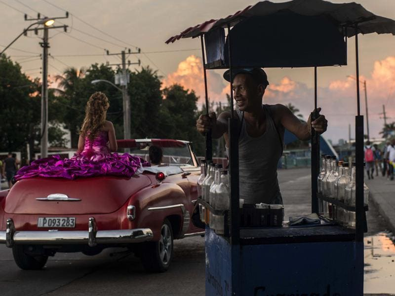 As per myths and legends of Latin America, girls were prepared to be married or become nuns. A soft drink vendor smiles as he watches Amanda Teresa Betancur, who lives in Cuba, ride in a classic American convertible, on her way to her quinceanera party in Havana, Cuba on December 13, 2015. The daughters of workers in Cuba's emerging private sector are helping fuel business. With the economic reforms, many families on the island now have extra cash to spend for quniceanera celebrations.  (AP)