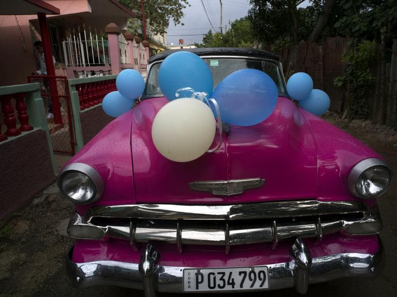 A classic American car sits decorated with balloons before taking Daniela Santos Torres, 15, to her quinceanera party in the town of Punta Brava near Havana, Cuba, December 20, 2015.  (AP)