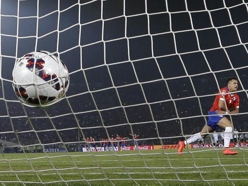 Champions of South America, finally: Chile's Alexis Sanchez calmly slots the ball into the goal for the winning penalty against Argentina before proceeding to take off his shirt in celebration as Chile won their first Copa America. (AP Photo)