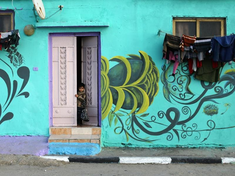 A Palestinian child looks out of a house painted by Palestinian artists in the al-Shati refugee camp in Gaza City, on December 19.  (AFP)