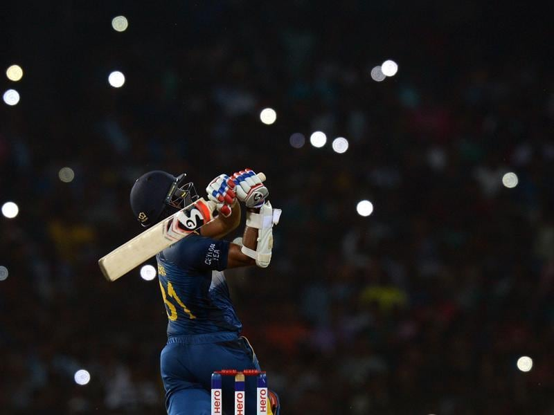 Sri Lankan cricketer Shehan Jayasuriya plays a shot as light from spectators' mobile phones are seen in the background during the second T20 match against the West Indies at the R Premadasa Stadium in Colombo on November 11, 2015. (AFP Photo)