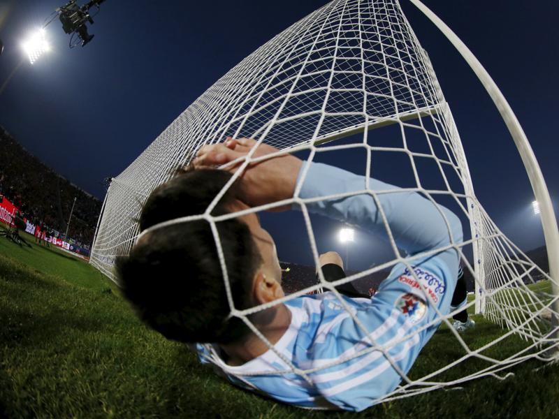 So close, yet so far for Messi's Argentina: Lionel Messi falls in the net during the Copa America final. After losing the 2014 World Cup final, Argentina fell short again, losing to Chile. (Reuters Photo)