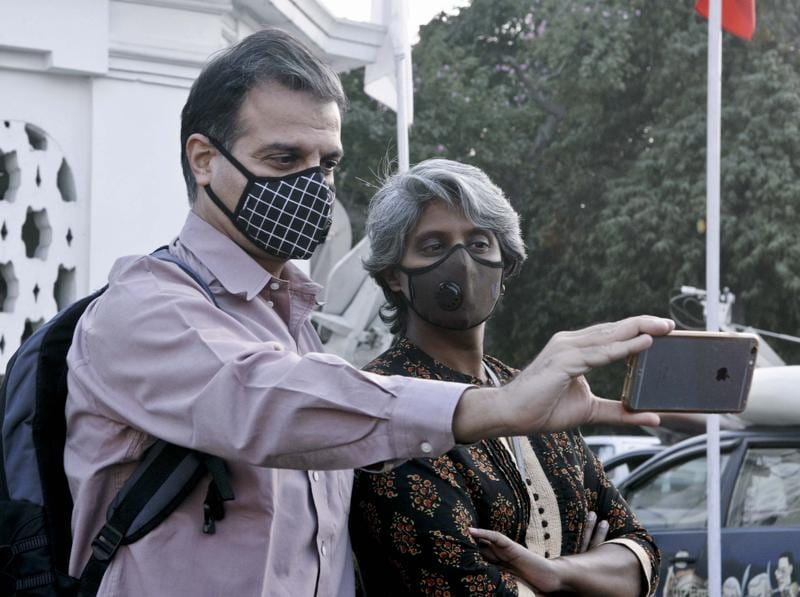 Delhi dialogue commission members take selfie wearing masks at the Delhi Assembly. (Sonu Mehta/ Hindustan Times)