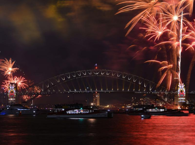 New Year's eve fireworks illuminate Sydney's iconic Harbour Bridge and Opera House during the traditional fireworks show held before the main midnight event on December 31, 2015.  (AFP PHOTO / Peter PARKS)