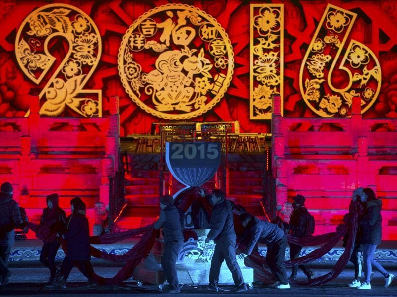 Workers push a 2016 countdown clock into position during a rehearsal for a New Year's eve countdown celebration at the Imperial Ancestral Temple in Beijing. At 8 hours ahead of Greenwich Mean Time, China will ring in 2016 ahead of much of the rest of the world on Thursday night.  (AP Photo/Mark Schiefelbein)